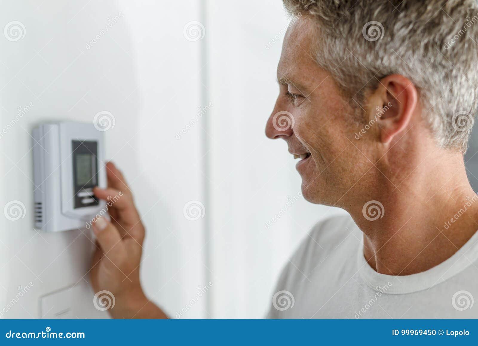 Het glimlachen van Mens het Aanpassen Thermostaat op Huis Verwarmingssysteem