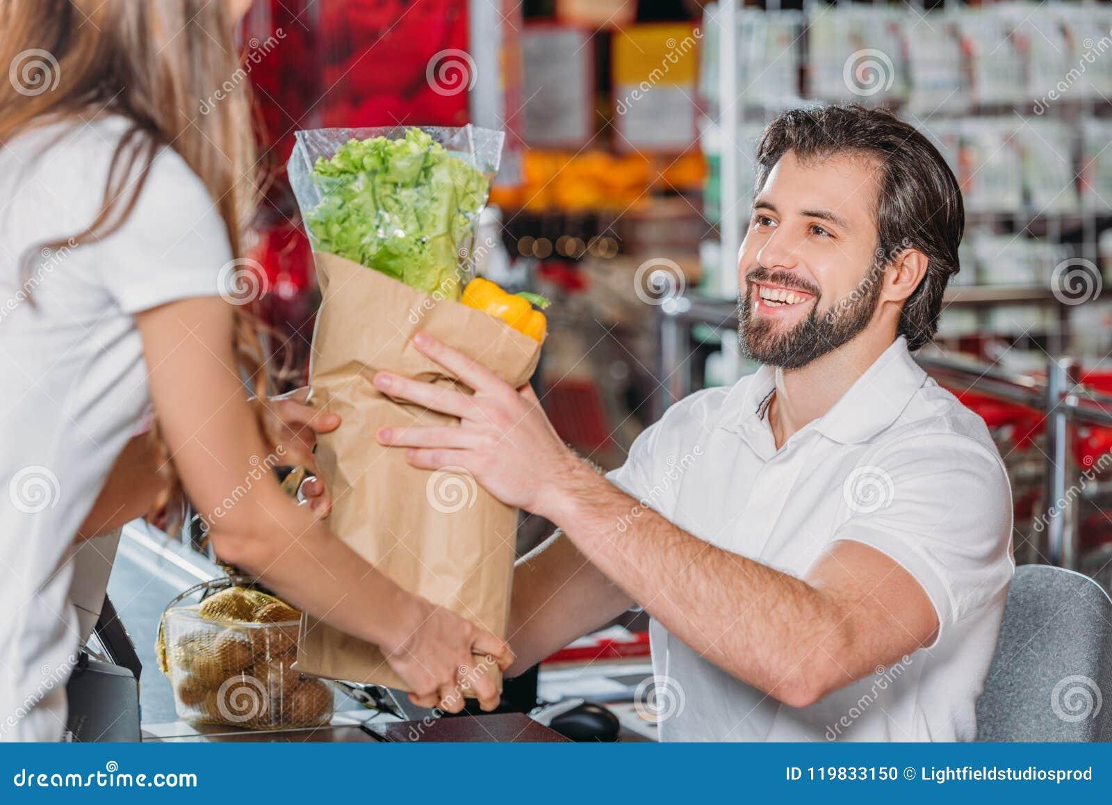 Het glimlachen winkel hulp gevende aankoop aan klant