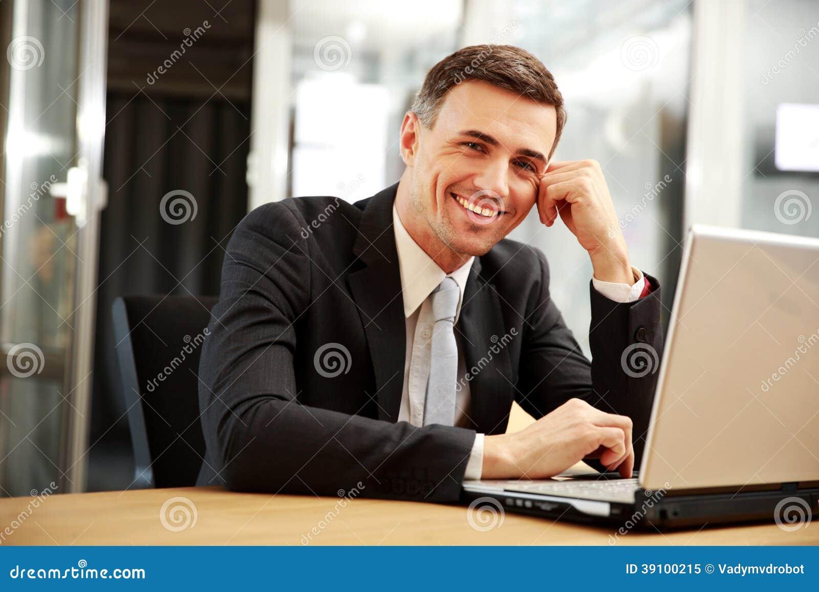 Het glimlachen zakenmanzitting met laptop