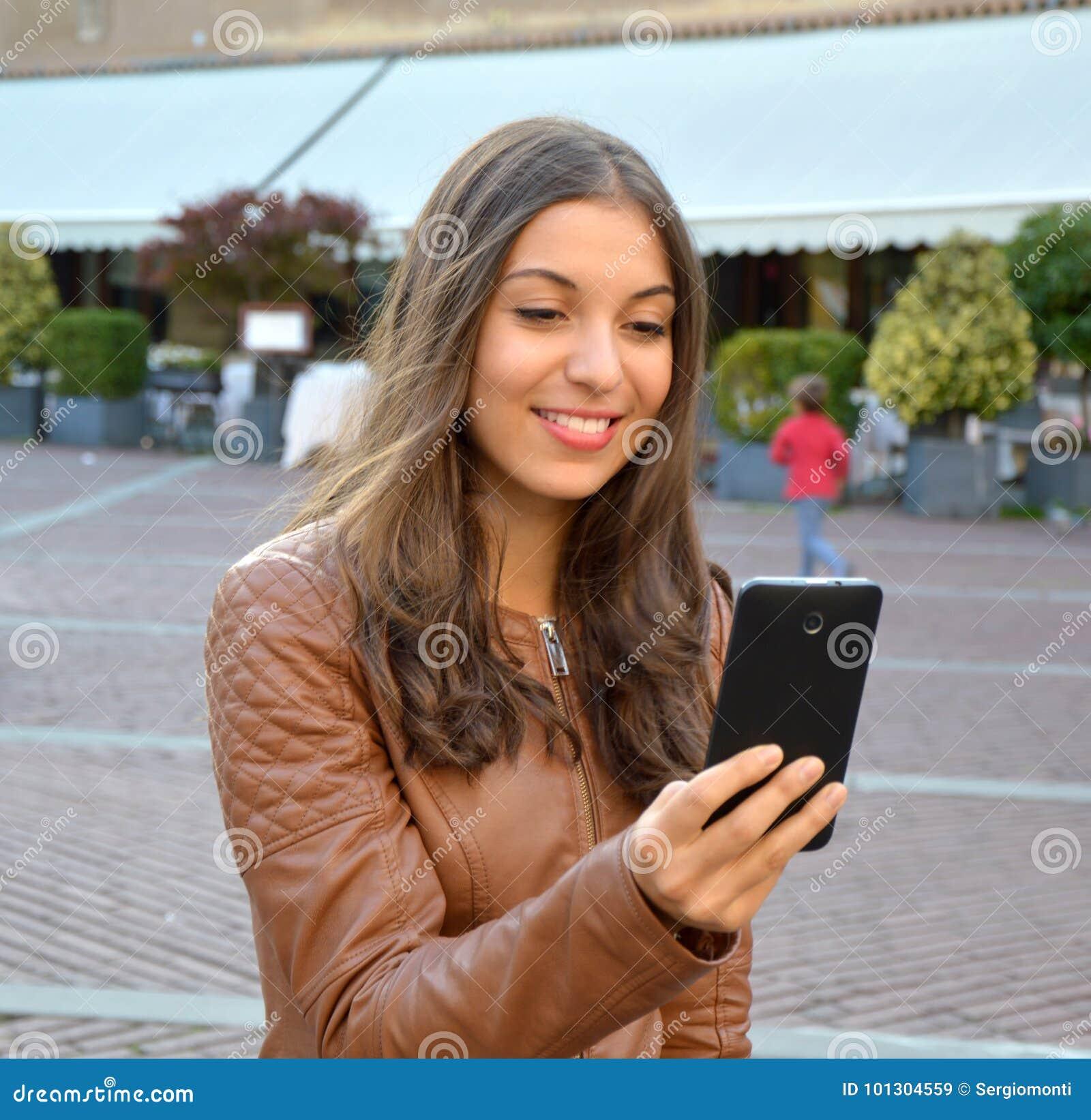 Het glimlachende hipster meisje leest prettig tekstbericht van haar vriend op mobiele telefoon openlucht