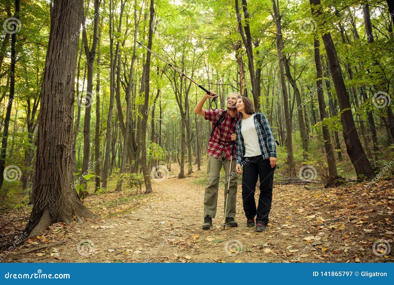 Het glimlachende jonge paar die door de bosmens wandelen richt aan een afstand