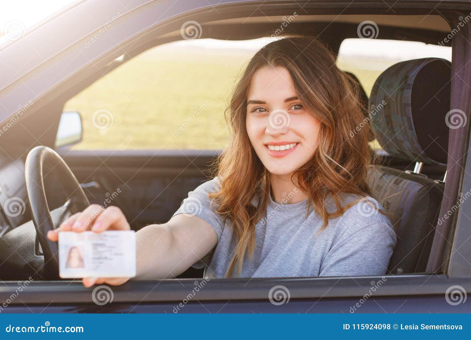 Het glimlachende jonge wijfje met prettige verschijning toont trots haar bestuurdersvergunning, zit in nieuwe auto, die jonge one
