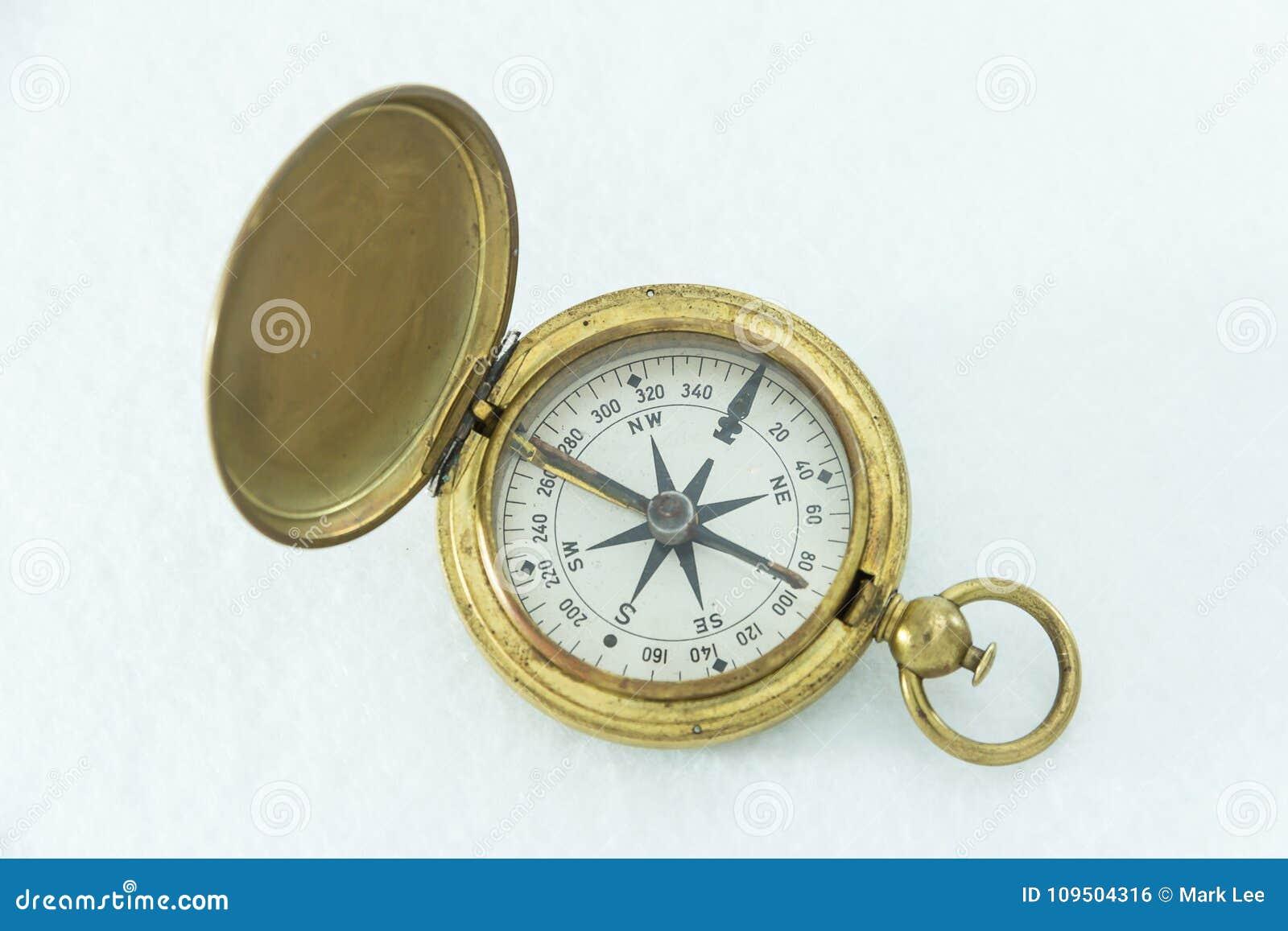 Het goed gebruikte militaire die kompas van de V.S. op witte achtergrond wordt geïsoleerd