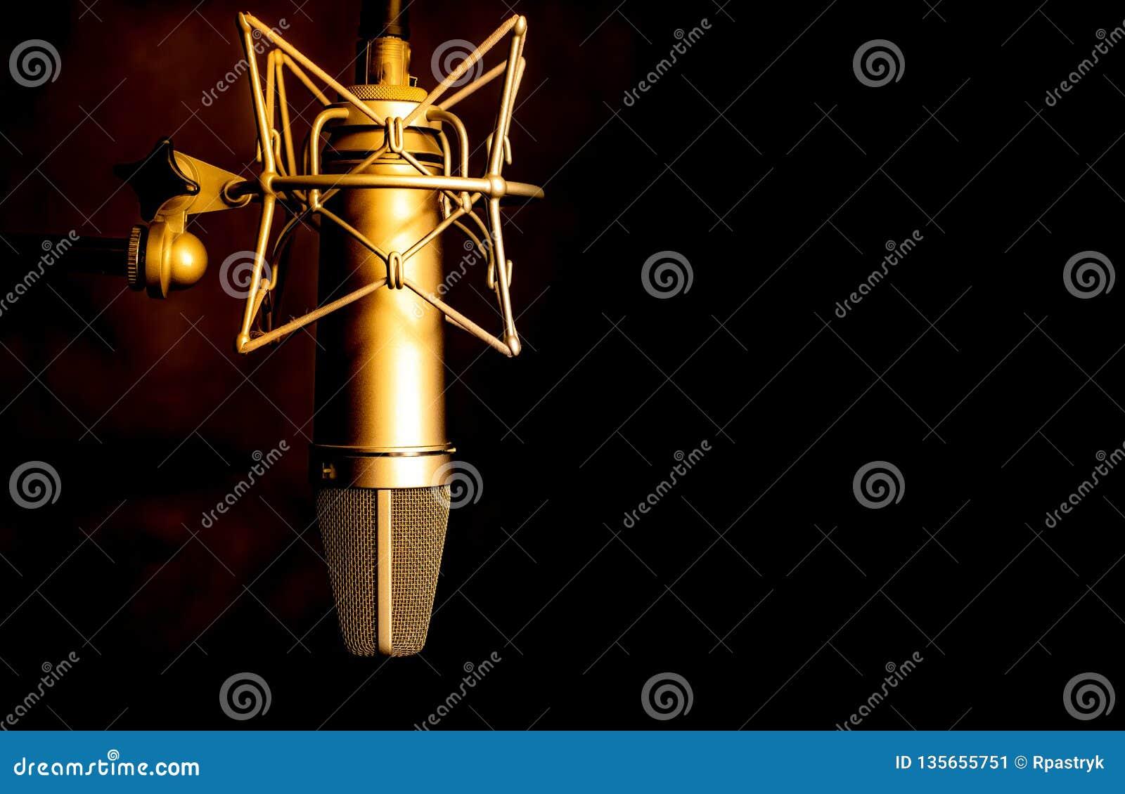 Het gouden detail van de kleurenmicrofoon in muziek en geluidsopnamestudio, zwarte achtergrond, close-up