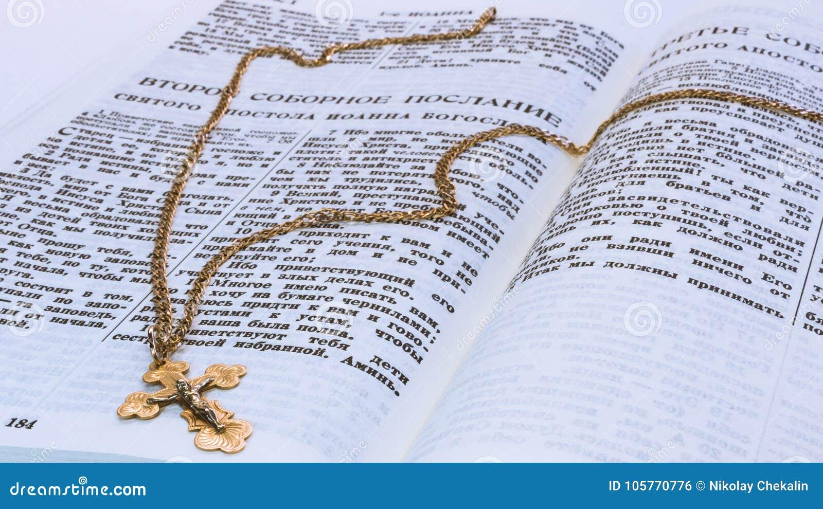 Het gouden kruis van de kruisiging van Christus op heilige scripture van de oude overeenkomst op de pagina met de tekst van de tw