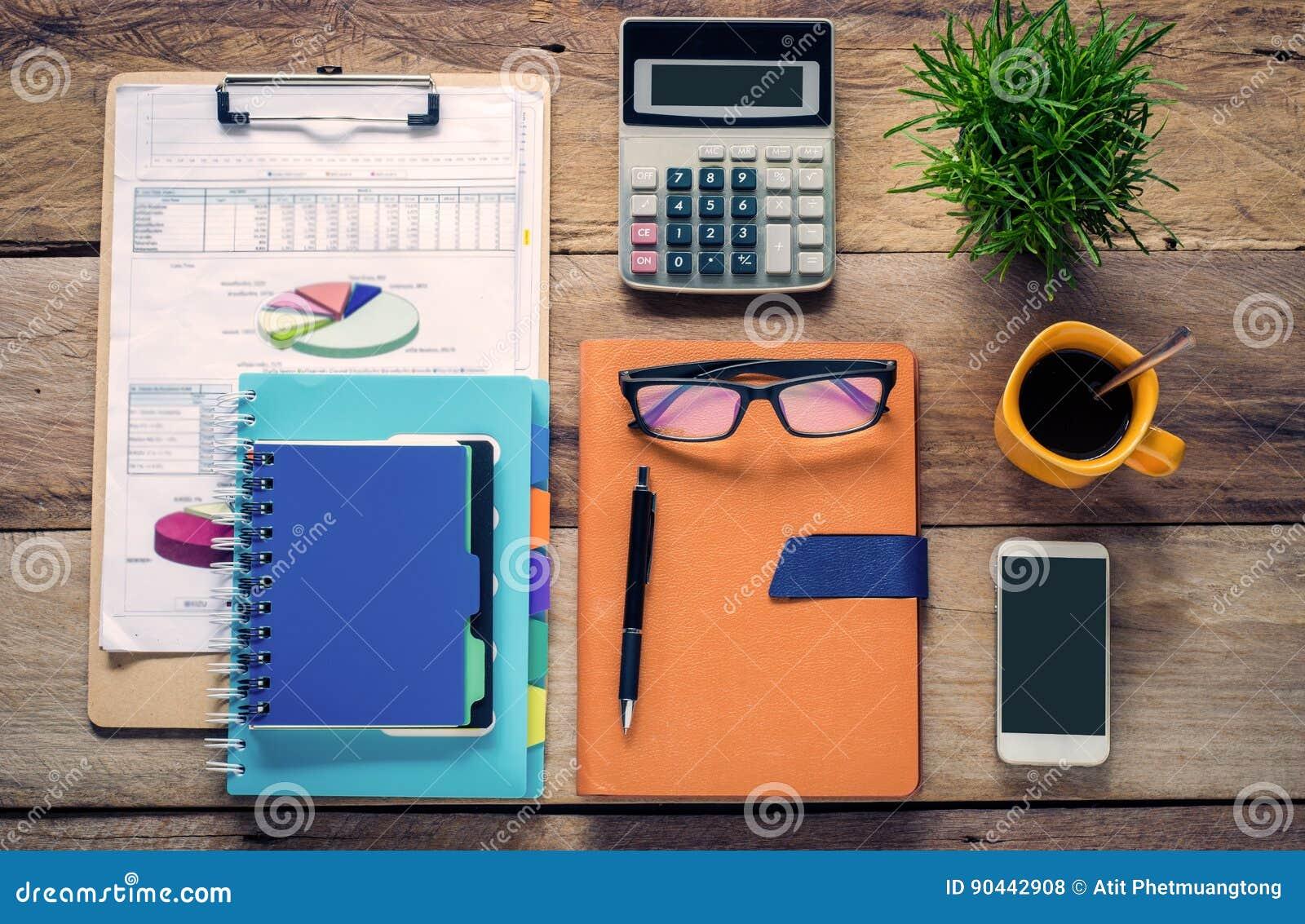 Het grafisch voorstellen, calculators, notitieboekjes, pennen, koffiekop en oogglazen op de houten vloer