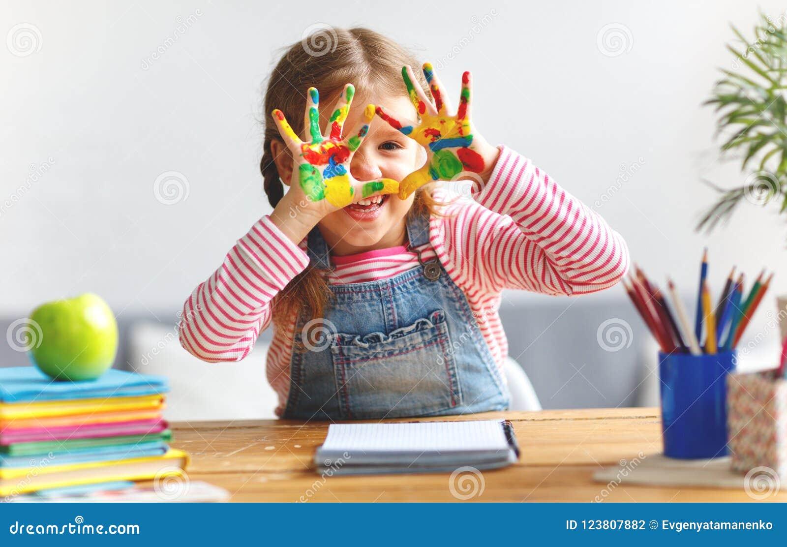 Het grappige kindmeisje trekt het lachen toont handen vuil met verf
