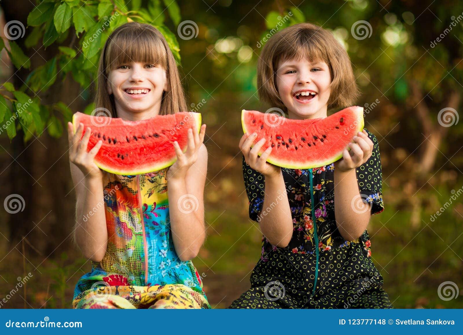 Het grappige kleine zustersmeisje eet watermeloen in de zomer