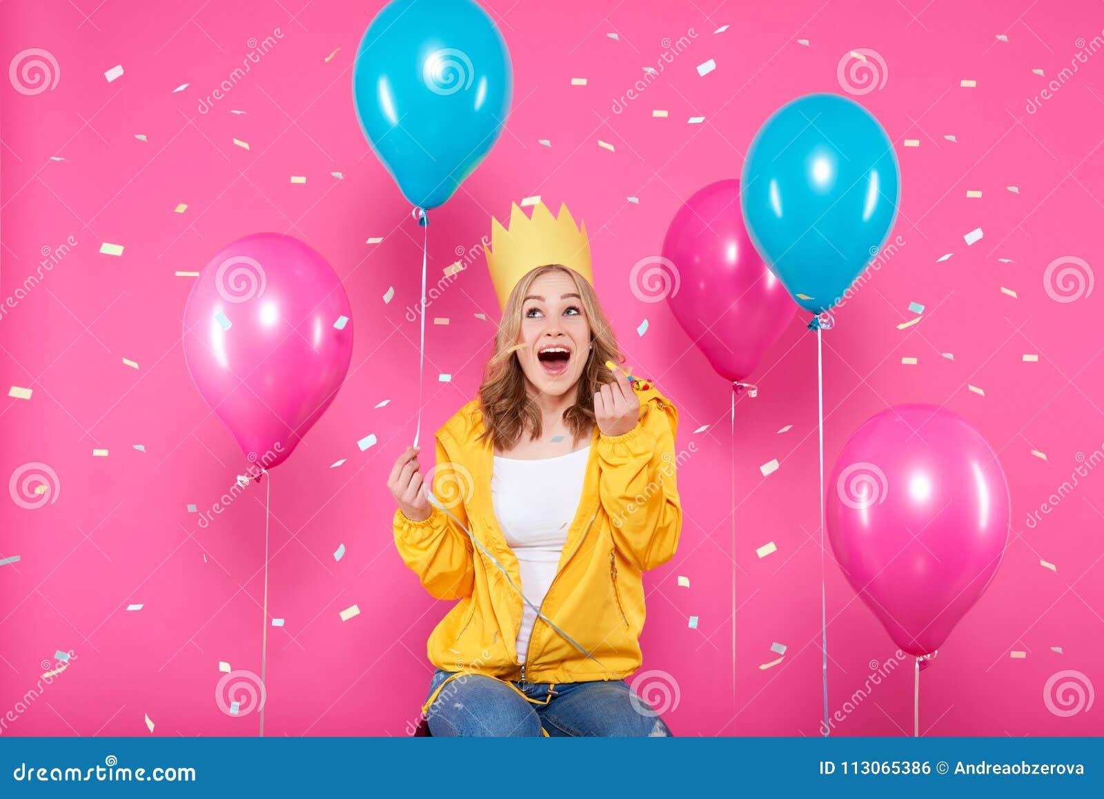 Het grappige meisje in verjaardagshoed, de ballons en de vliegende confettien op pastelkleur doorboren achtergrond Aantrekkelijke