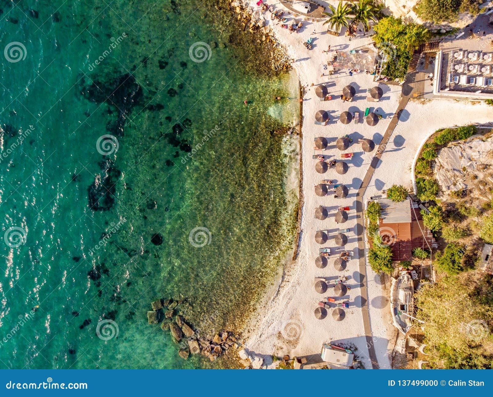 Het Griekse Strand met zand en duidelijk blauw watertop down satellietbeeld schoten het gebruiken van een hommel