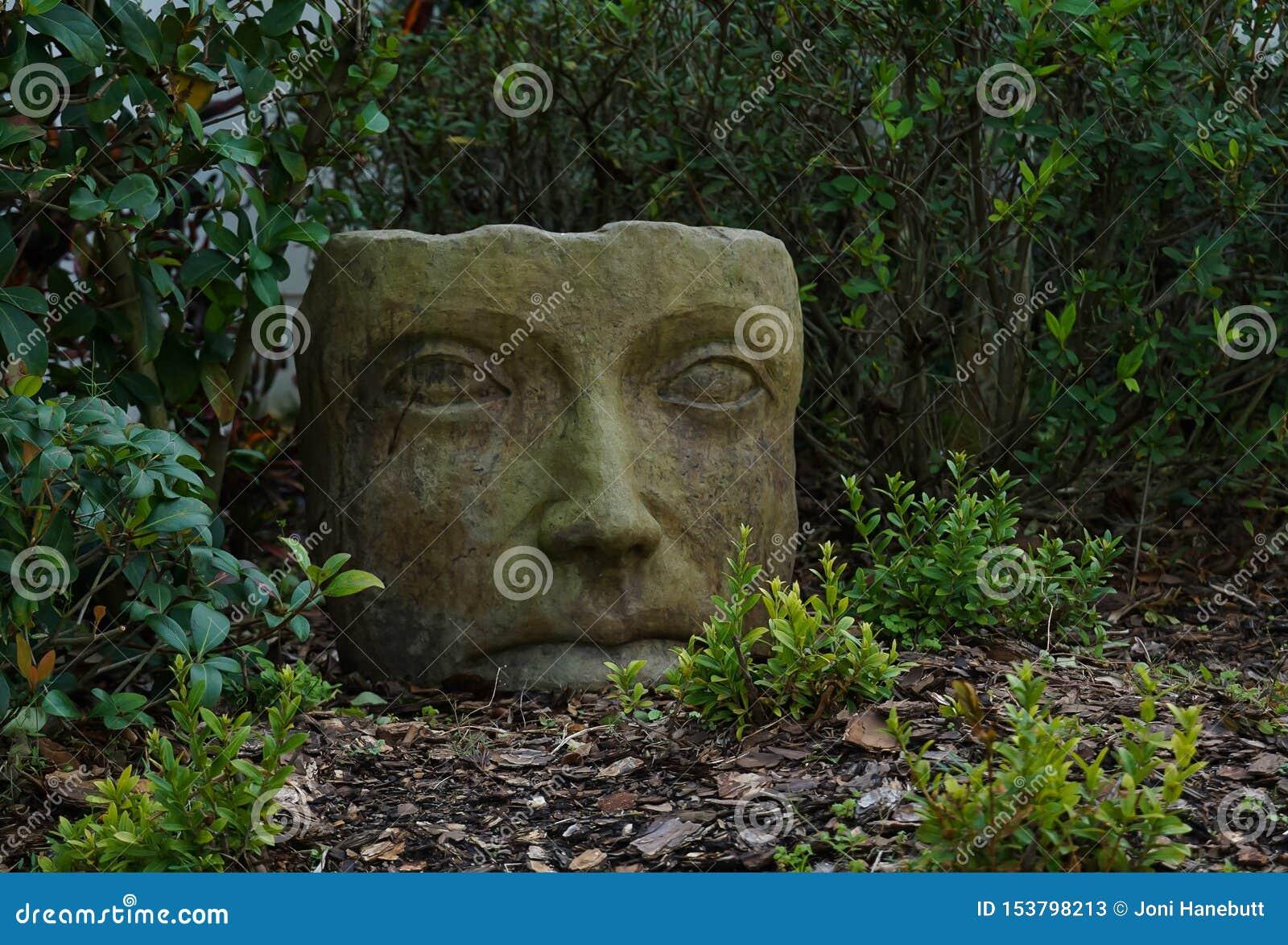 Het grijze standbeeld van de steen Aziatische tuin