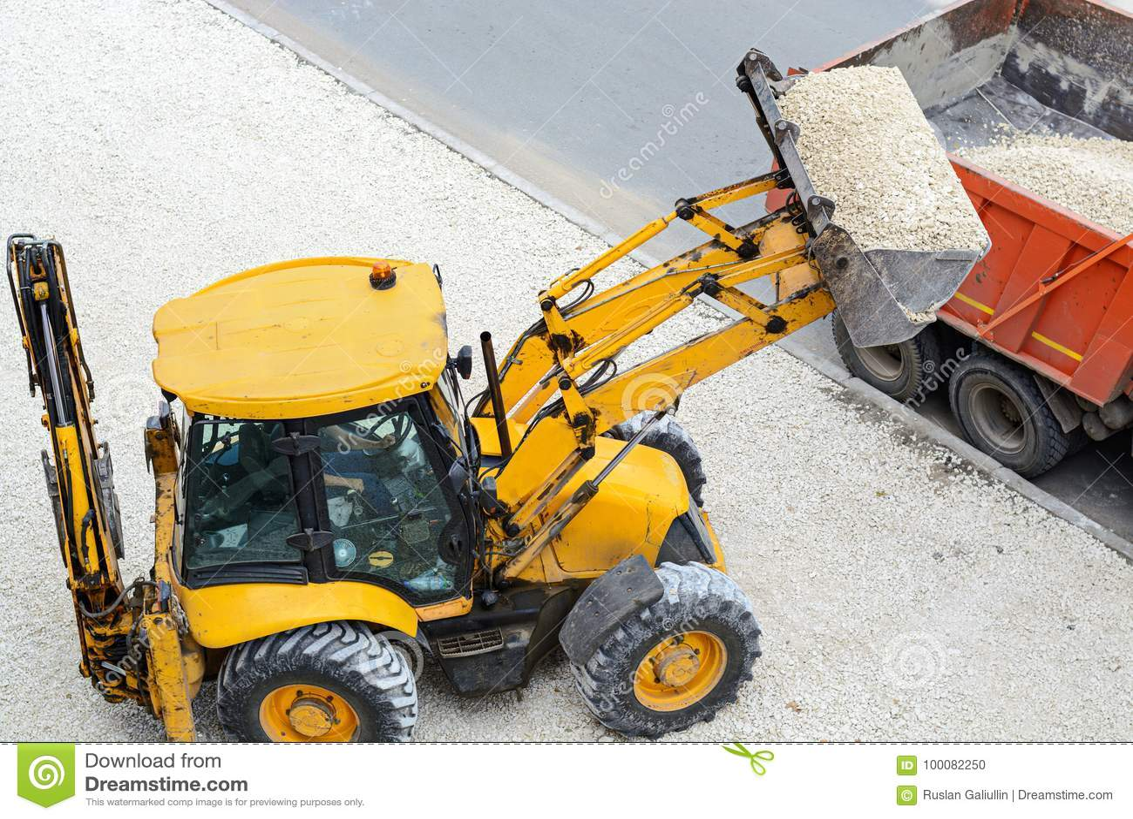 Het grint van de tractorlading in een vrachtwagen De werken van de weg