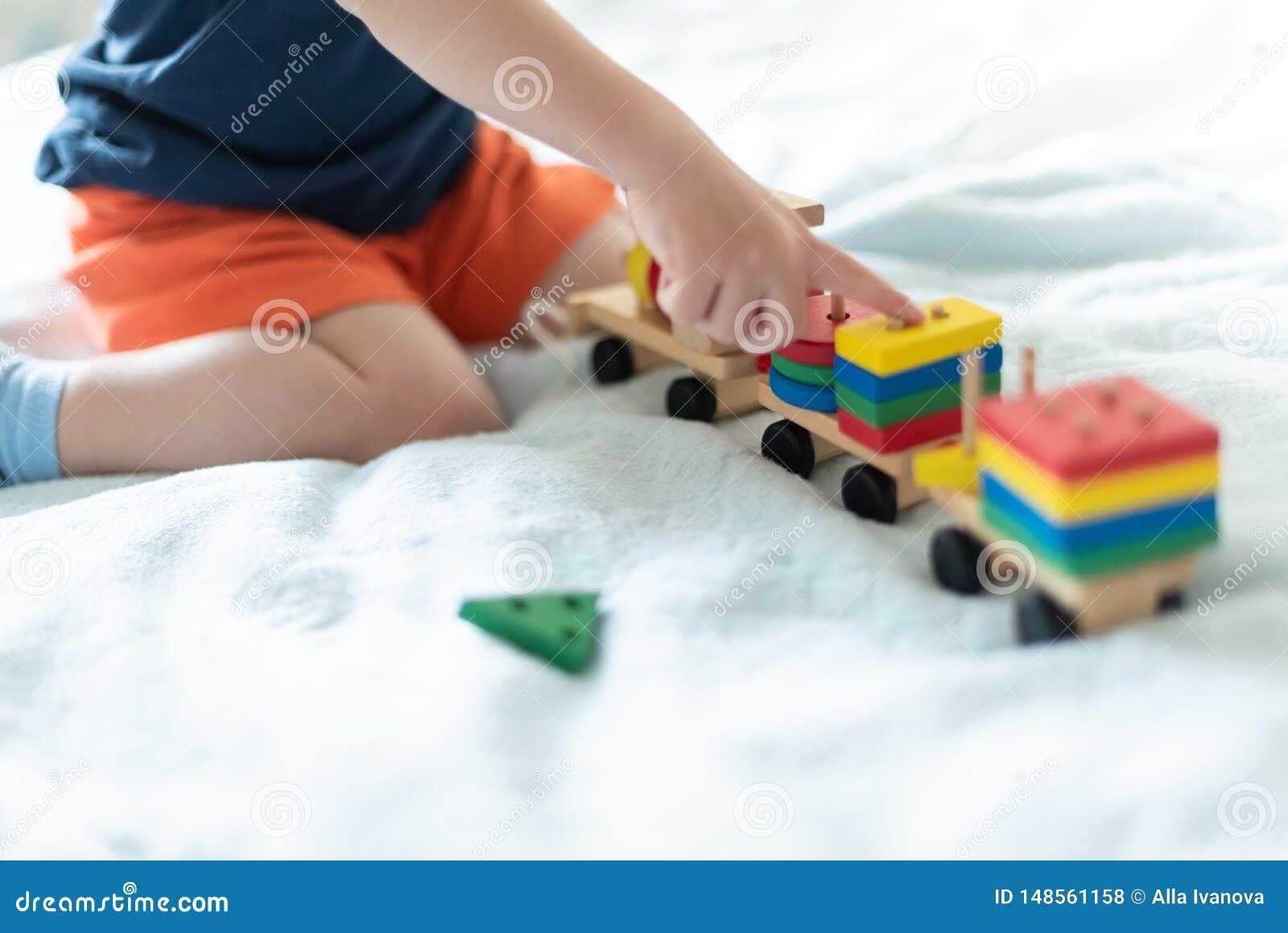 Het groeien en het concept van de jonge geitjesvrije tijd Een kind die met een gekleurde houten trein spelen Het jonge geitje bou