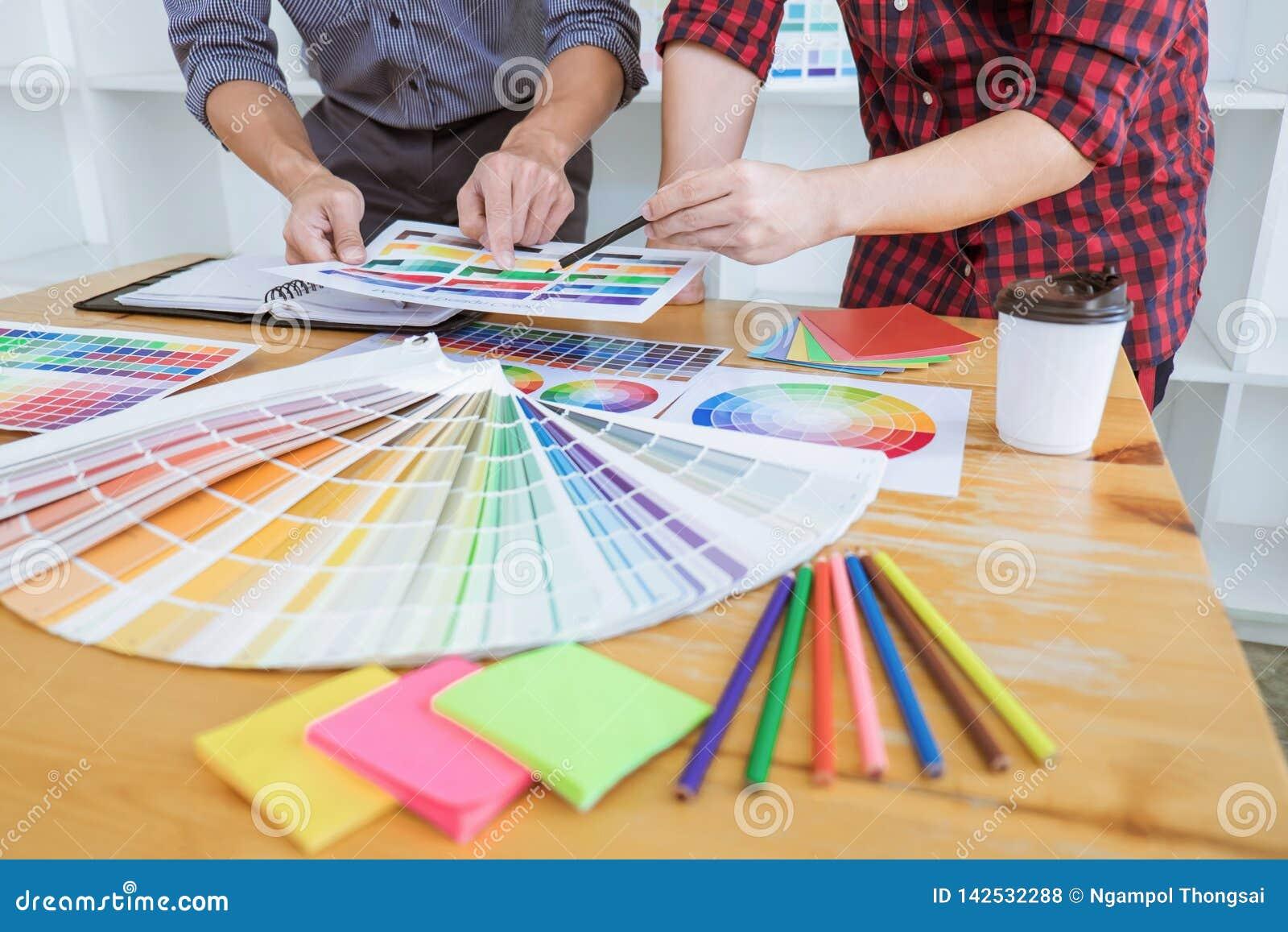 Het groepswerk van jonge creatieve ontwerpers die aan project samenwerken en kiest de steekproeven van het kleurenmonster voor se