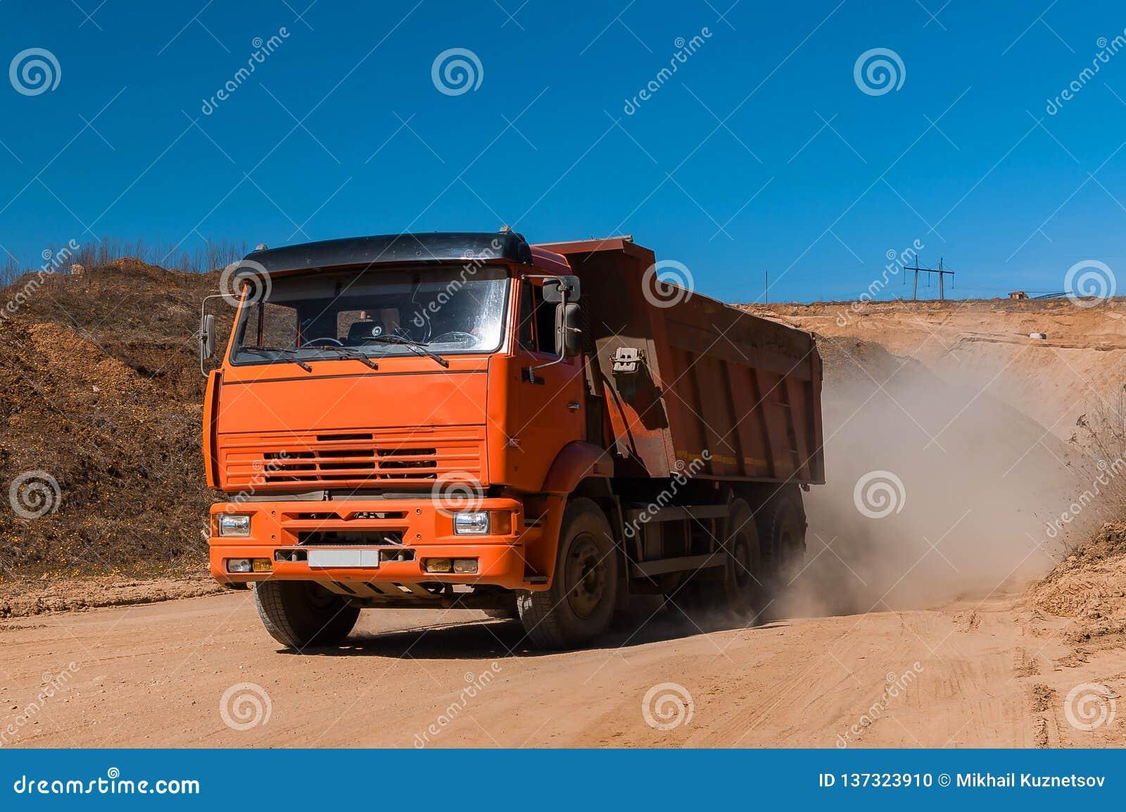 Het grote bewegende vuil van de stortplaatsvrachtwagen bij een nieuw commercieel project van de ontwikkelingsbouw