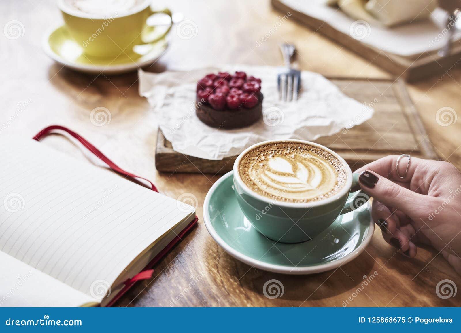 Het hebben van lunch met het koekje van de koffie vlak witte en zoete chocolade in een koffie of een restaurant De vrouwenhand ho