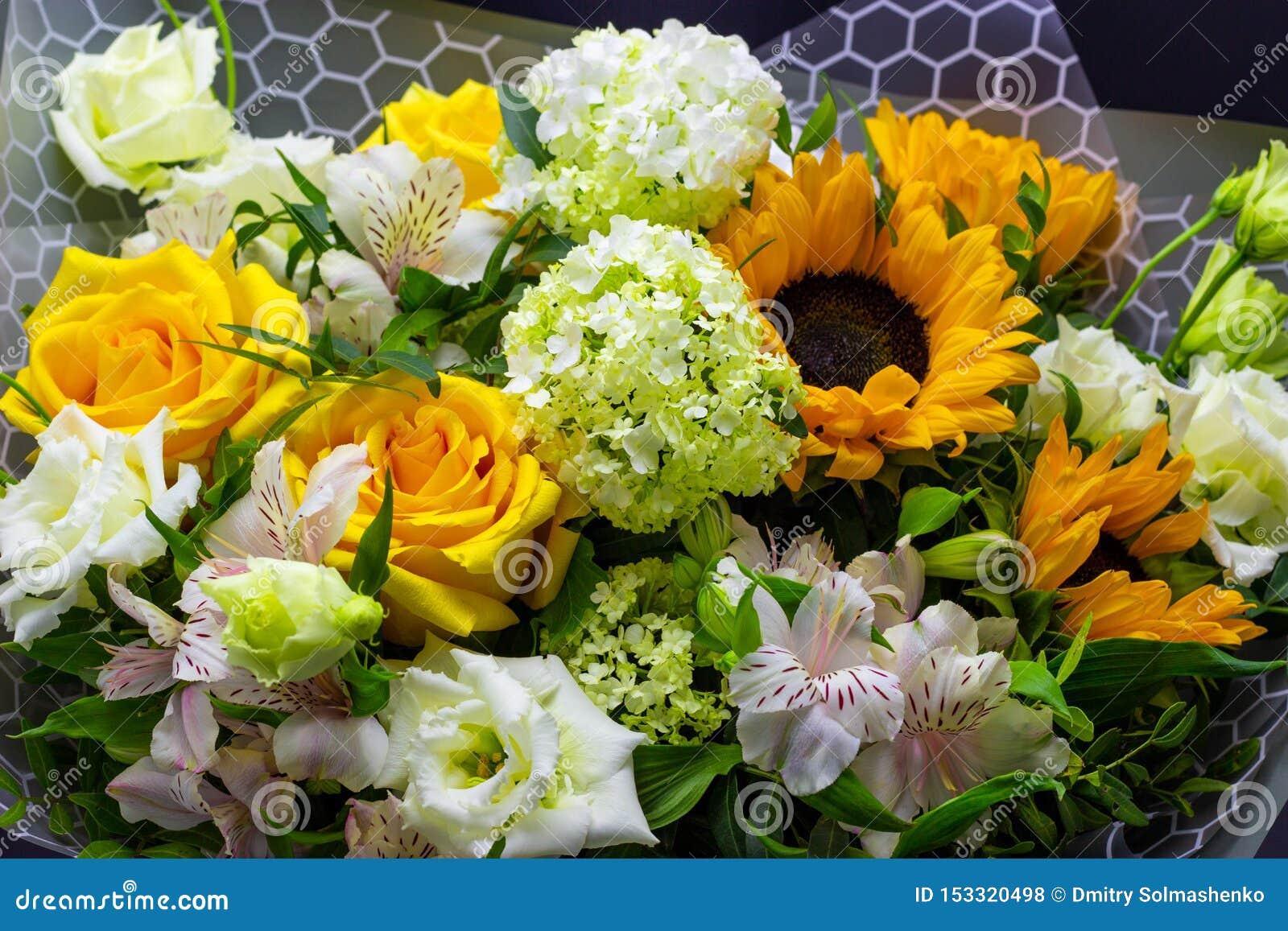 Het heldere boeket met gele zonnebloemen en nam, roze eustoma en groene viburnum bloemenachtergrond toe