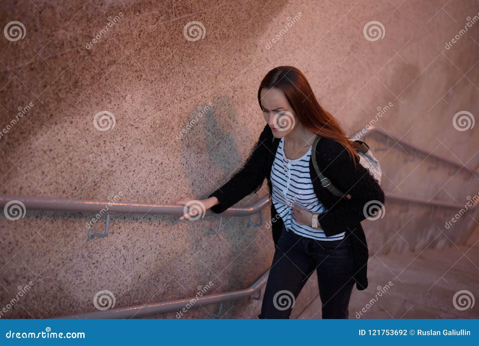Het helft-lengte portret van de hoogste mening van een jong meisje op de treden van de metro, de overgang houdt op een zieke stom