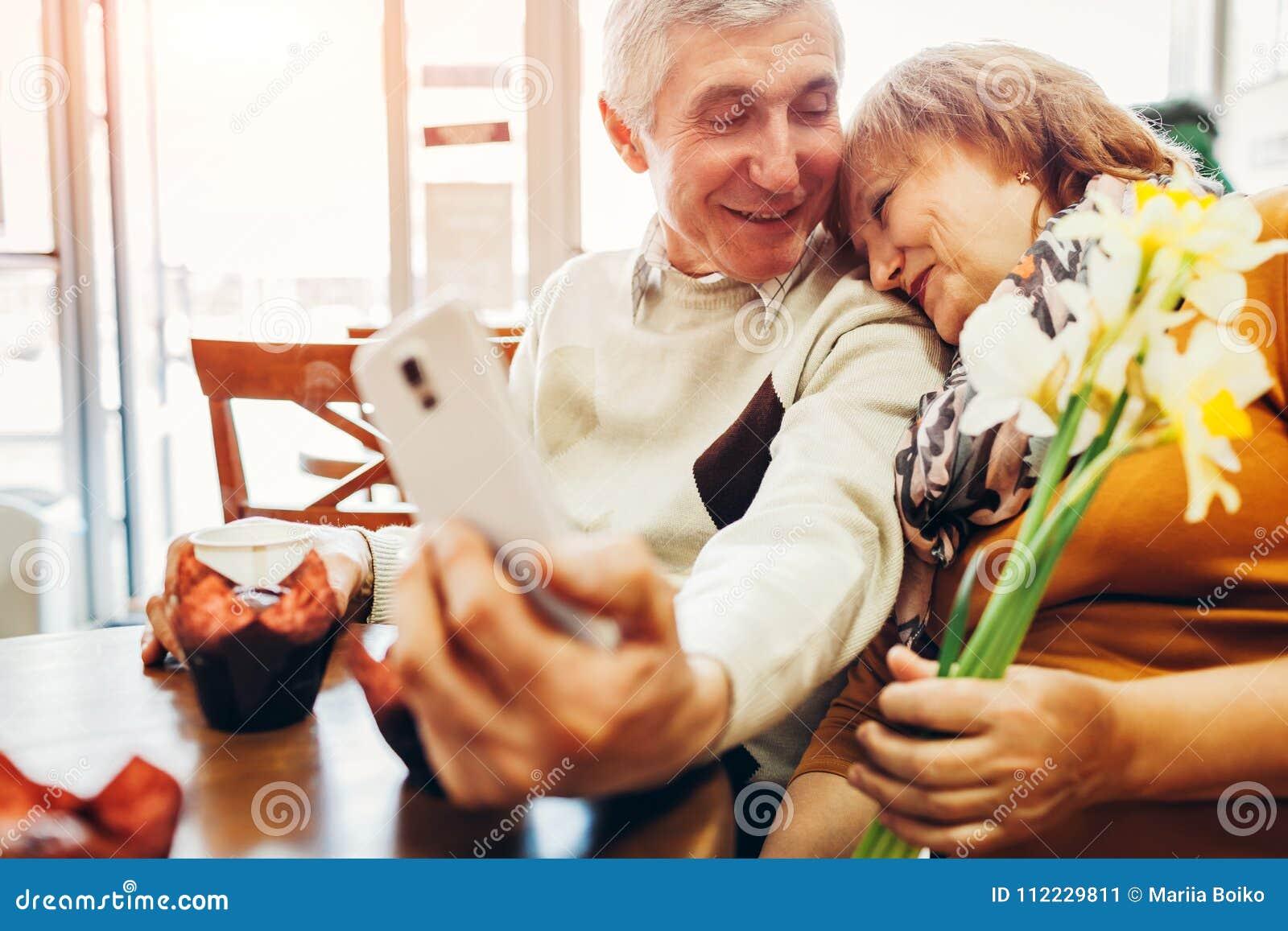 Het hogere paar maakt een selfie gebruikend een telefoon in de koffie Het vieren verjaardag