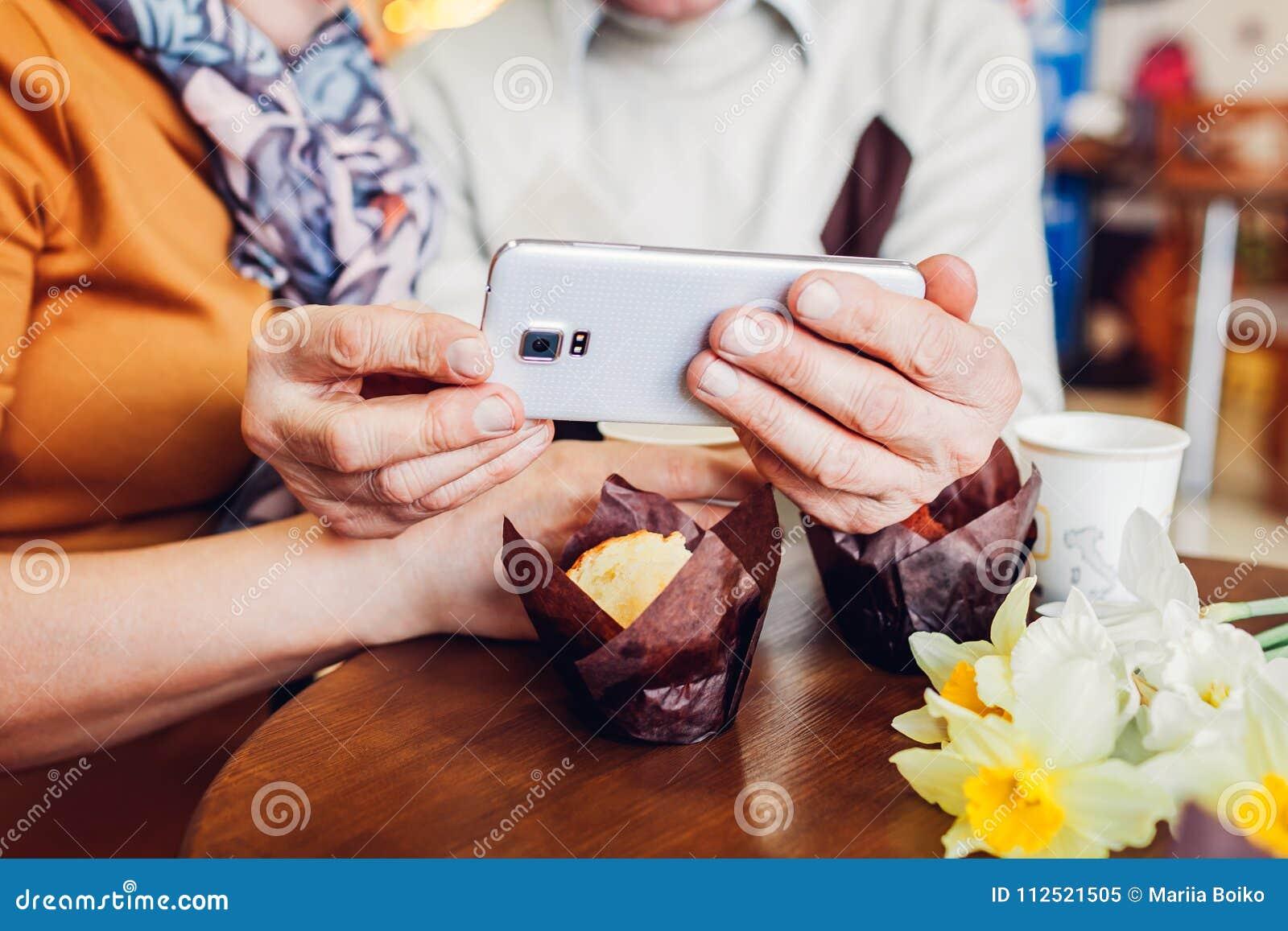 Het hogere paar maakt een selfie gebruikend een telefoon in de koffie Het vieren verjaardag Close-up