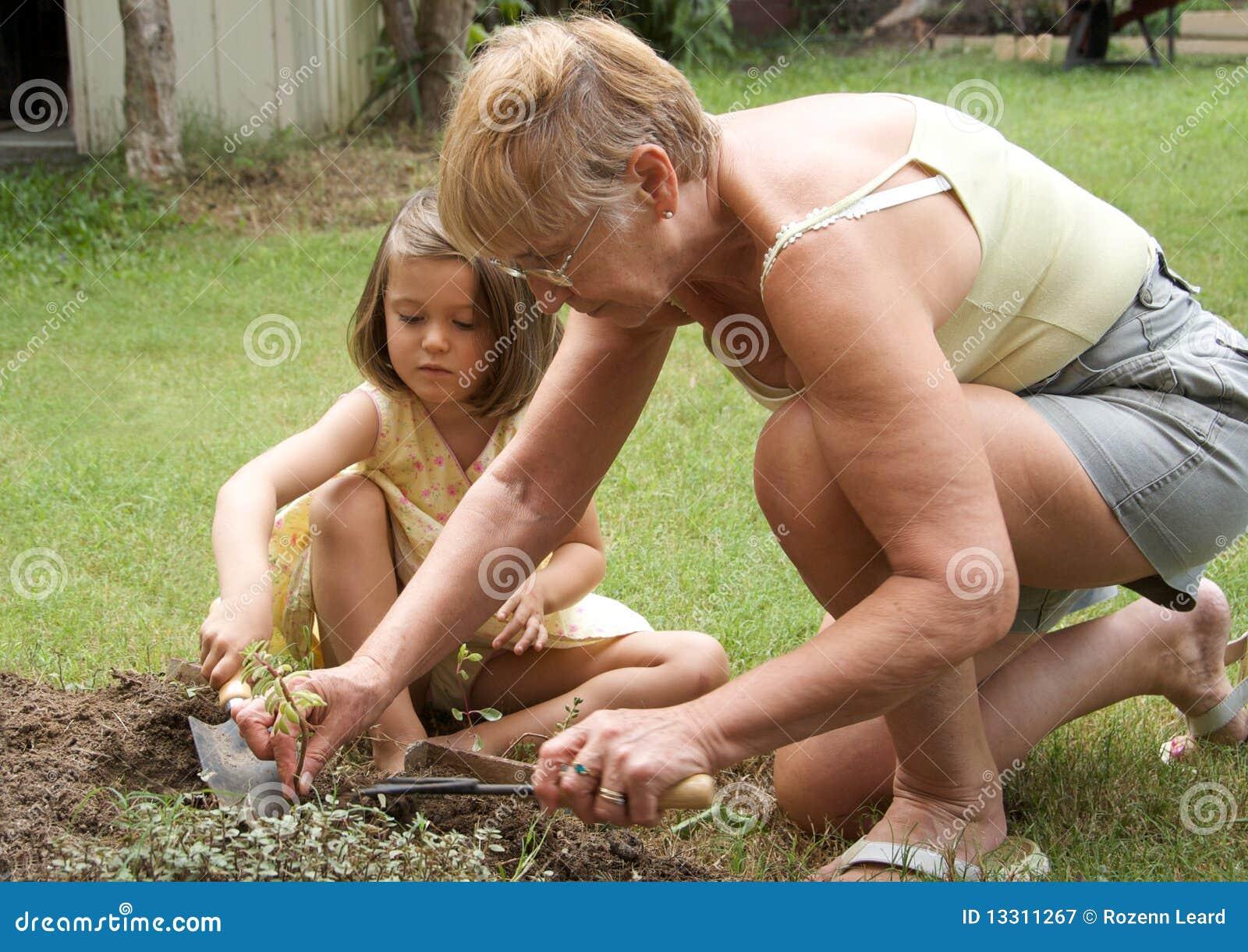 Het hogere vrouw en kind tuinieren