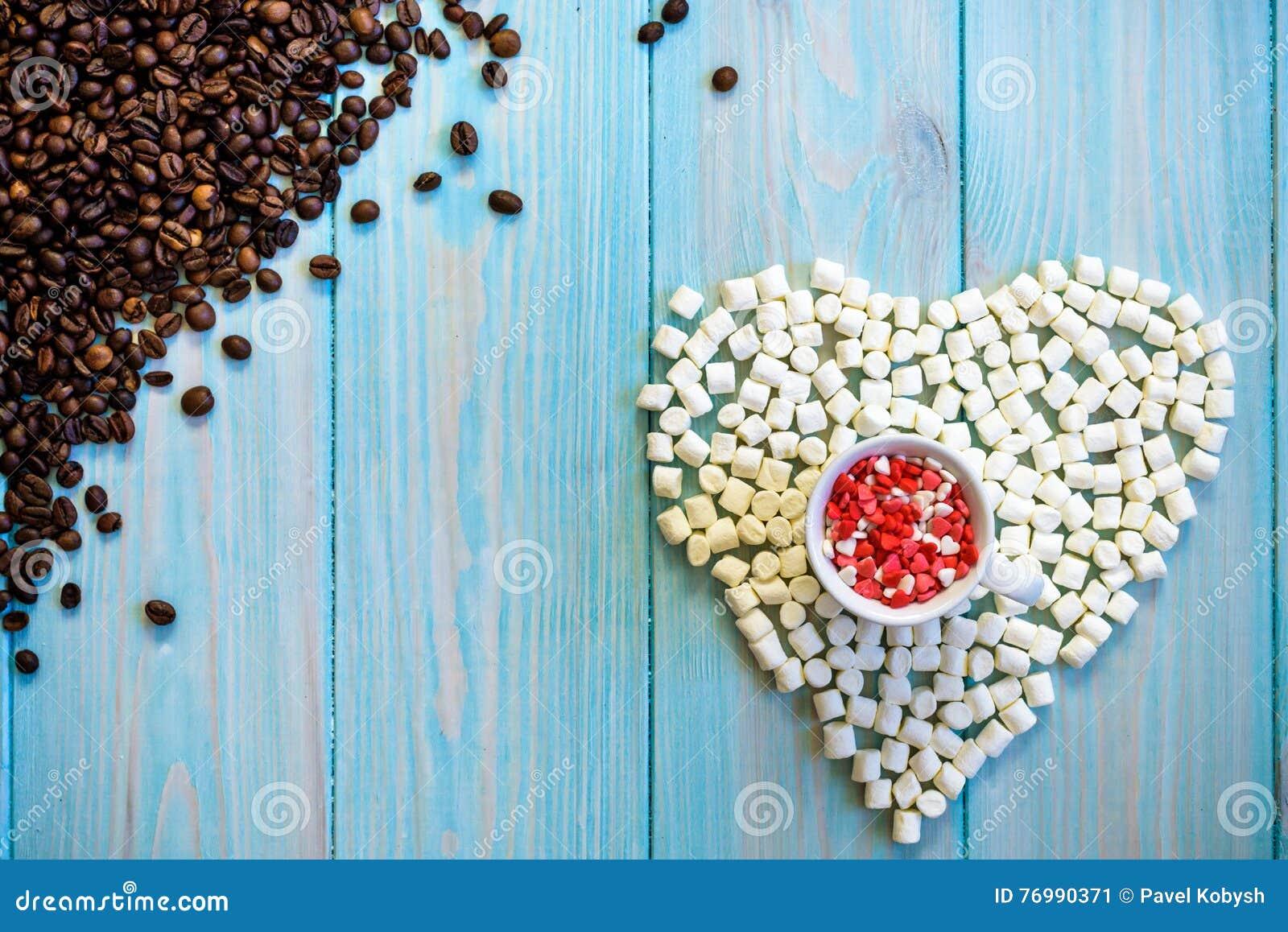 Het hoogtepunt van de koffiekop van suikergoedvlakte legt op rustieke lichtblauwe houten achtergrond Hartcijfer van Heemst wordt