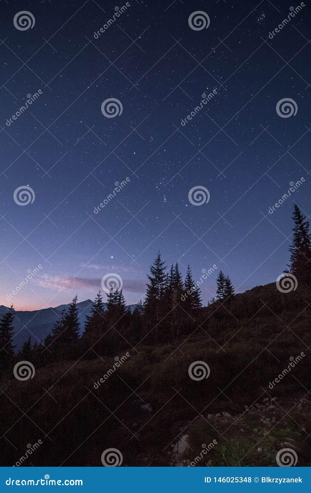 Het hoogtepunt van de nachthemel van sterren vlak vóór zonsopgang in bergen