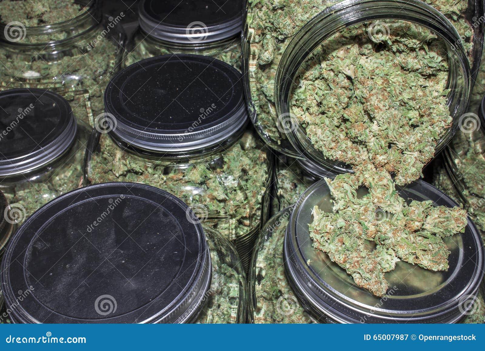 Het Hoogtepunt van glaskruiken van Marihuanaknoppen die uit morsen