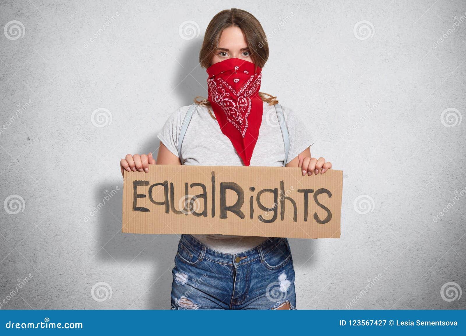 Het horizontale schot van mooi jong wijfje behoort tot feministische beweging, draagt rode bandana op gezicht, houdt plaat met in