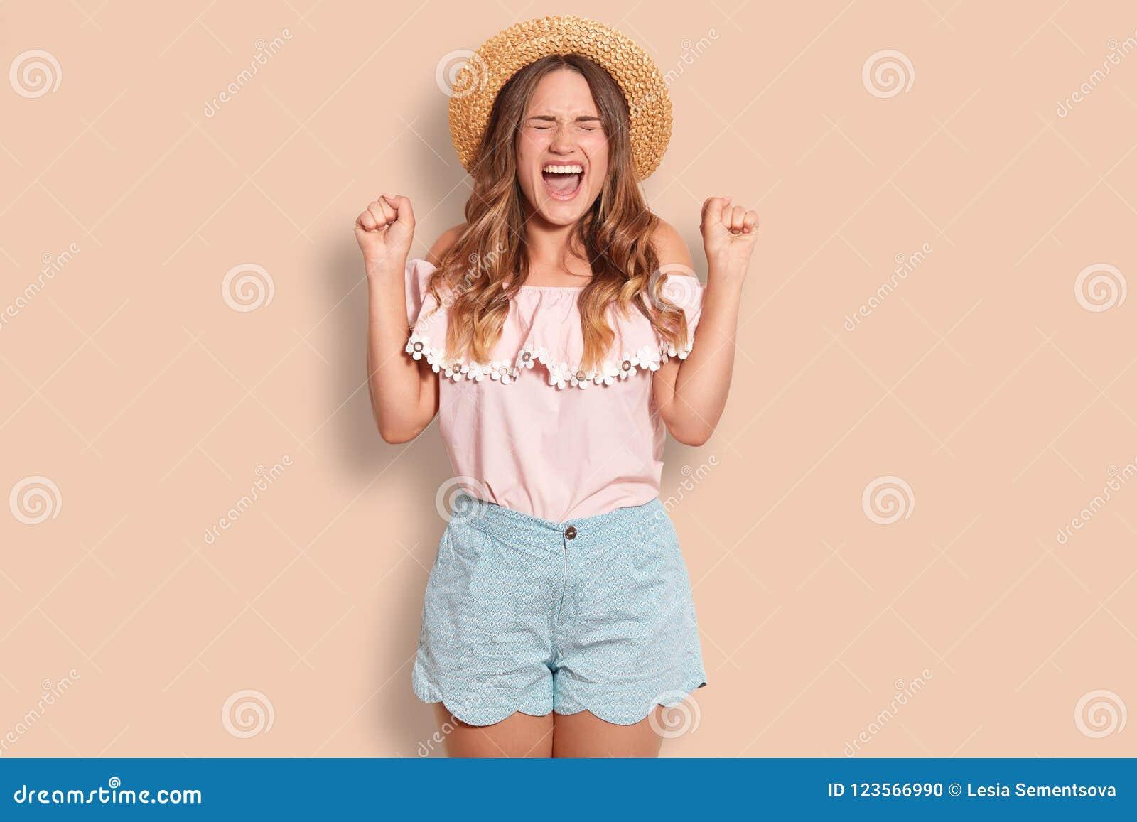 Het horizontale schot van vrolijk jong Europees wijfje klemt vuisten dicht, uitroept met geluk, sluit ogen, draagt de zomerhoed,