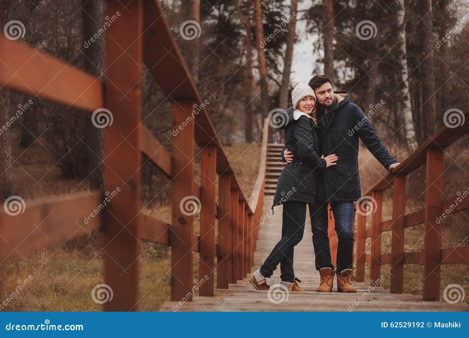 Het houden van jonge paar gelukkige samen openlucht op comfortabele warme gang in bos