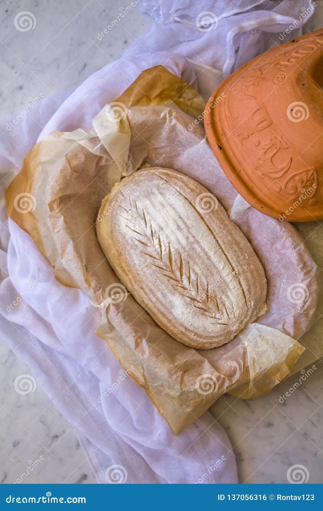 Het huis maakte tot Zuur deeg Artisanaal Gespeld Brood in het maken in een Nederlandse oven vóór het bakken op marmeren achtergro