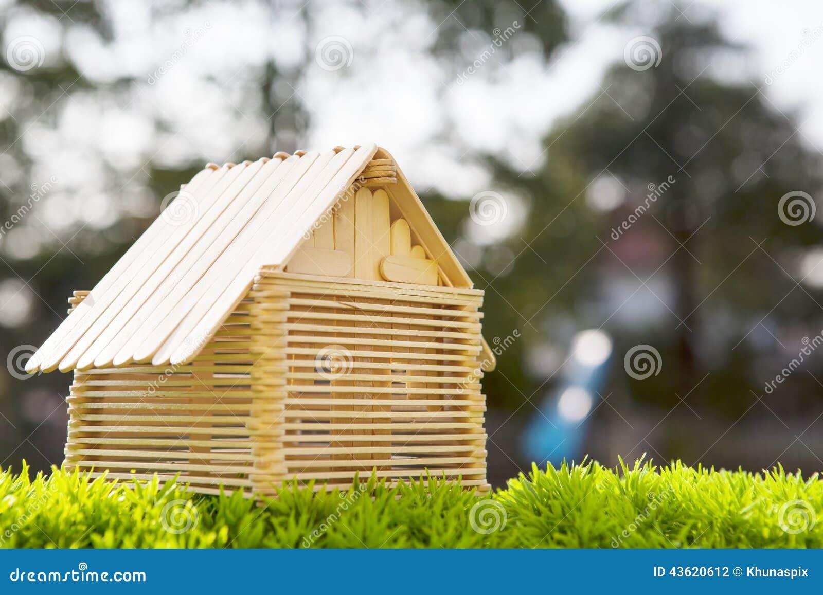 Het huismodel maakt van houten stok op kunstmatige gra