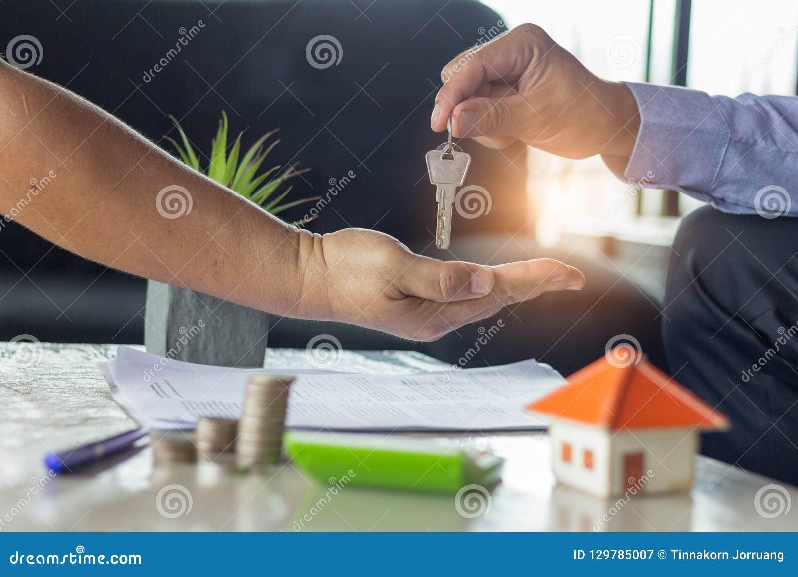 Het huissleutel van de makelaar in onroerend goedholding tot zijn cliënt na het ondertekenen