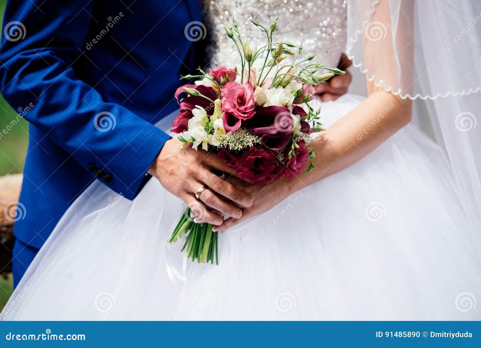 Het huwelijksboeket van Bourgondië bloeit in bruid ` s en bruidegom` s handen