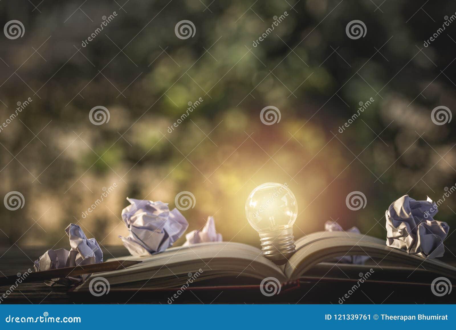 Het idee van het concept Het kweken van gloeilamp op uitstekend boek met verfrommeld p