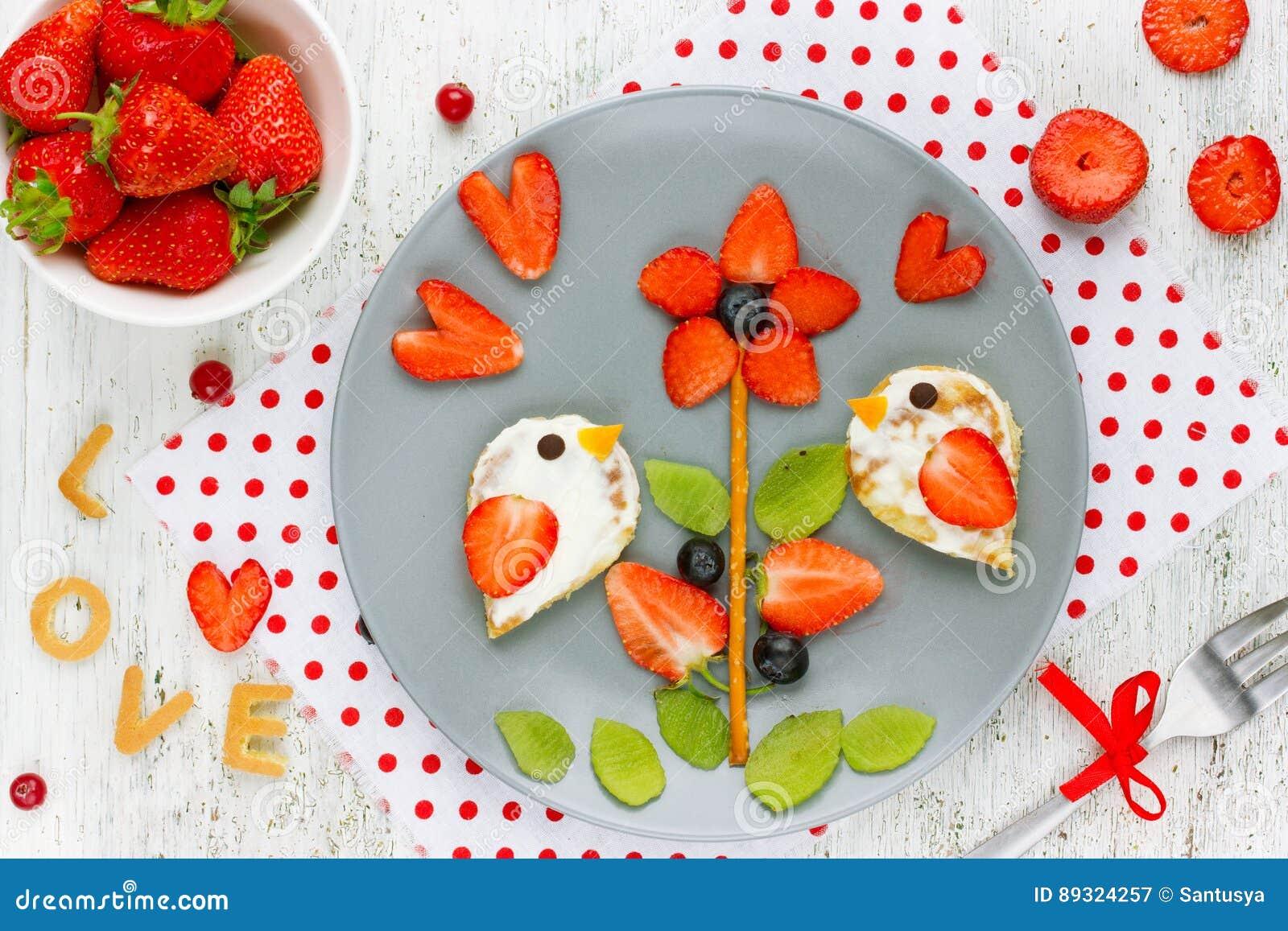 Het idee van de voedselkunst voor jonge geitjes - vogelpannekoeken met het blauw van de aardbeikiwi