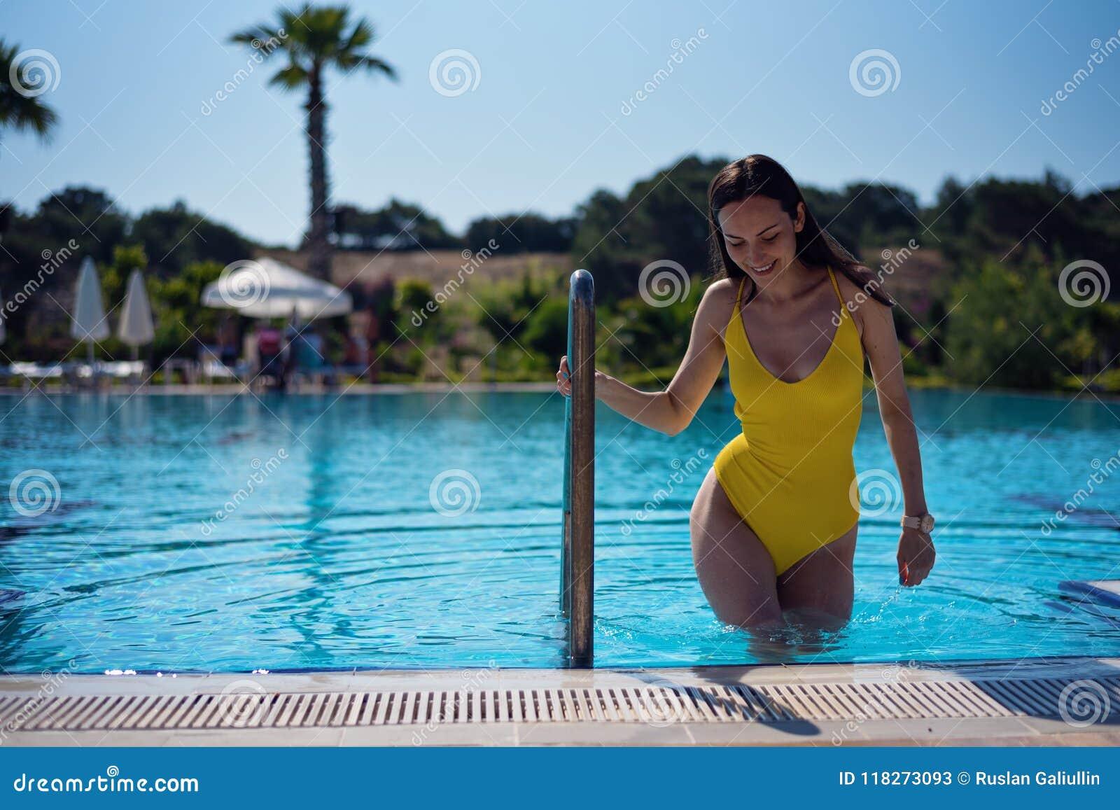 Het jonge aantrekkelijke brunette in mooie heupen komt uit de pool die op de leuning houden