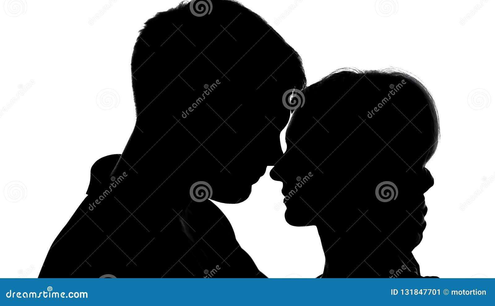 Het jonge aantrekkelijke paar silhouetteert passionately het kussen, sterk gevoel, liefde