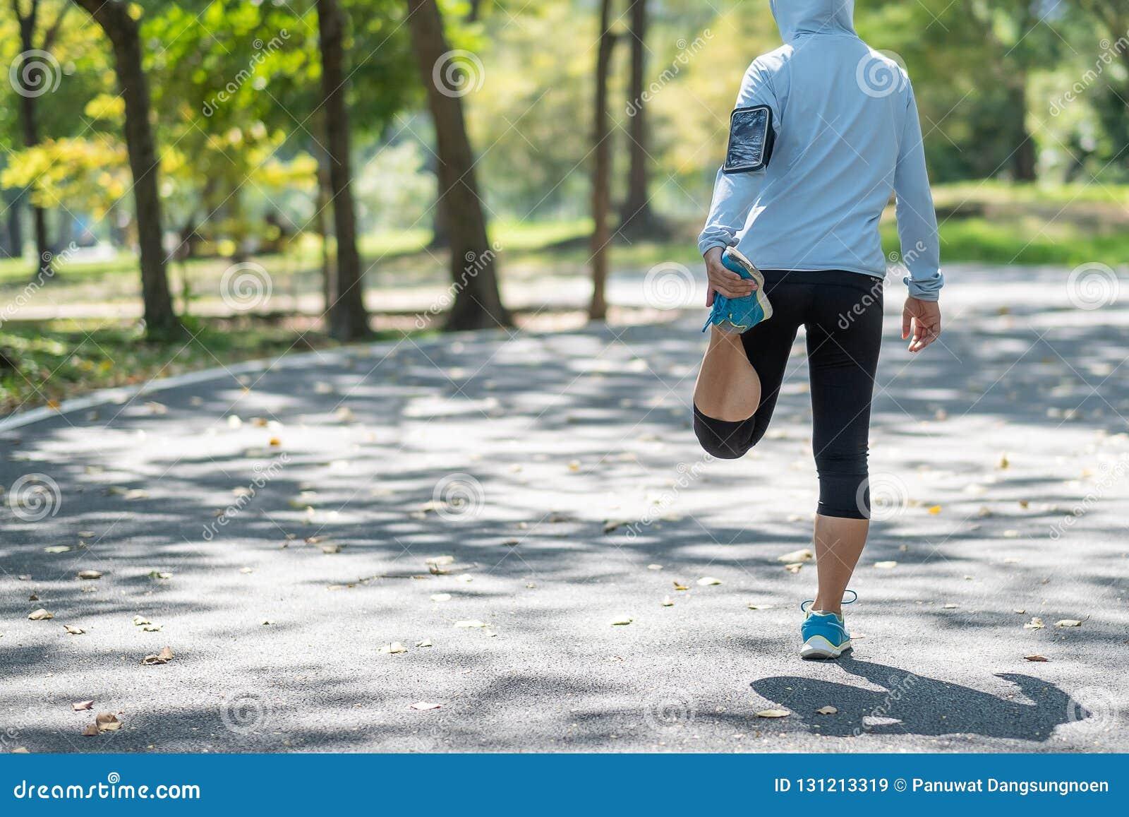 Het jonge atletenvrouw streching in de opwarming van de park openlucht, vrouwelijke agent klaar voor jogging op de weg buiten, Az