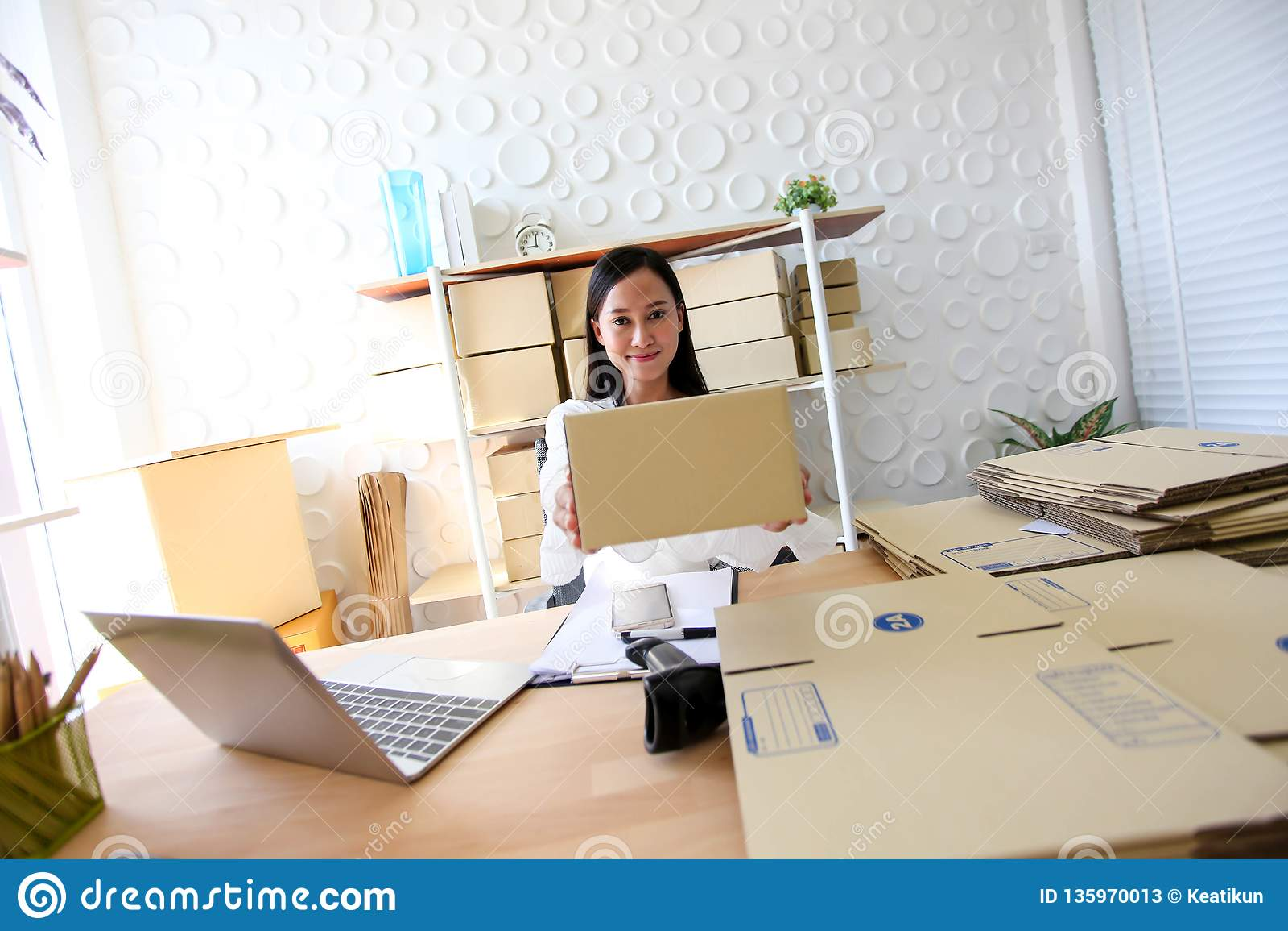 Het jonge Aziatische meisje is freelancer Start kleine het bedrijfseigenaar schrijven adres op kartondoos op werk, die het winkel