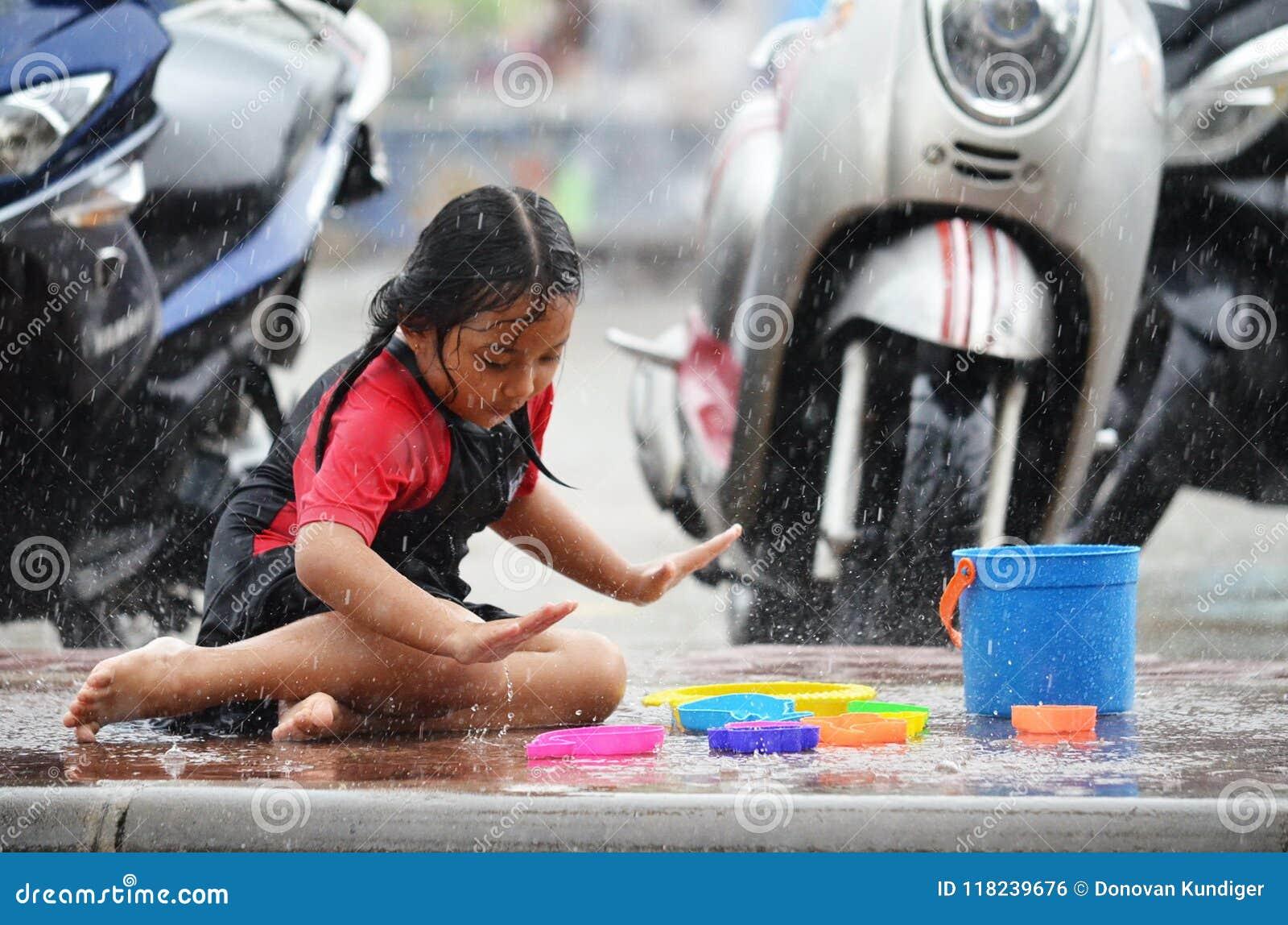 Het jonge Aziatische meisje houdt van speel in de regen tijdens moessonseizoen in Thailand