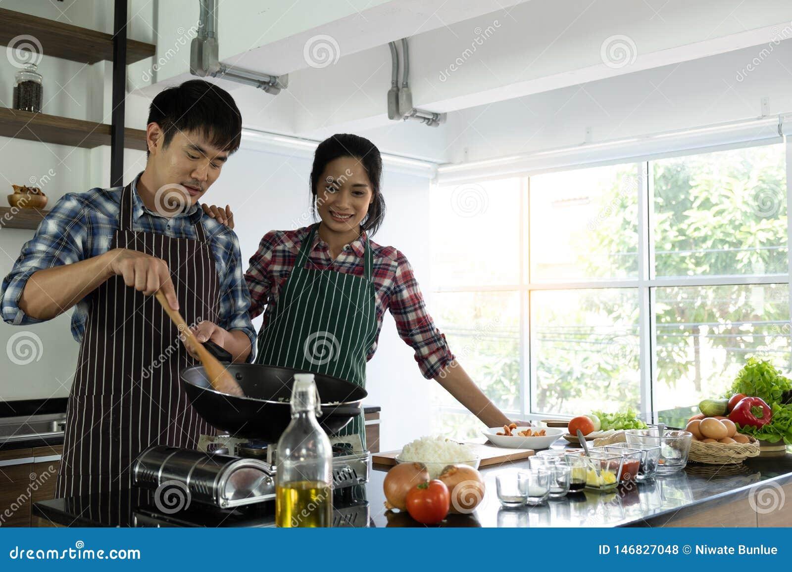 Het jonge Aziatische paar is gelukkig samen te koken