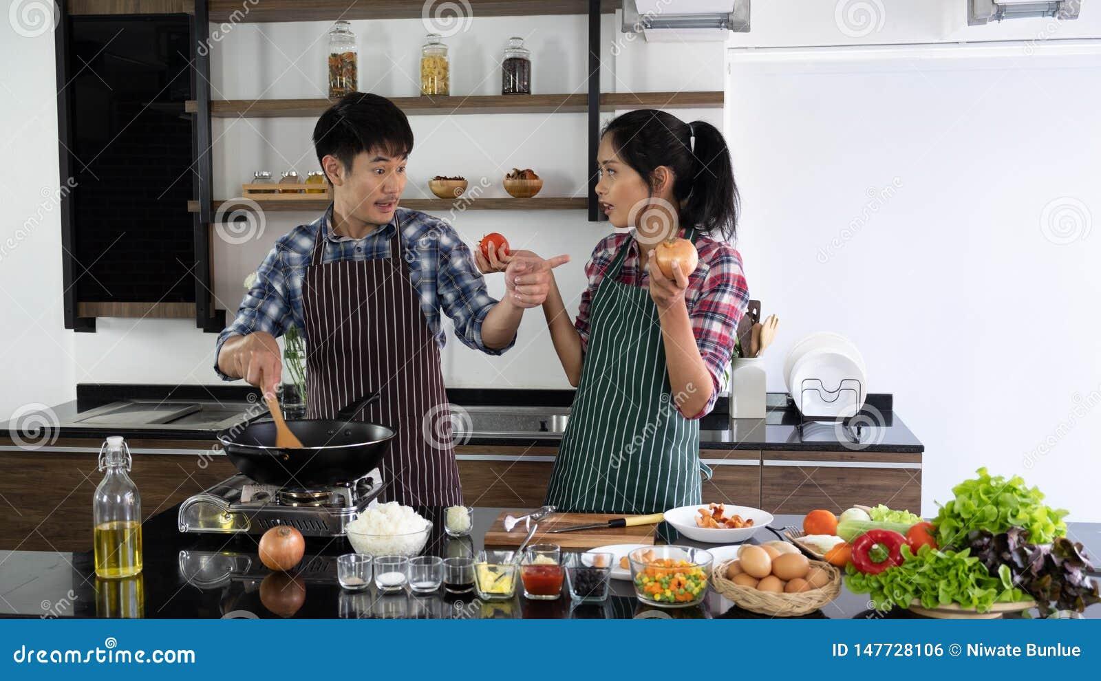 Het jonge Aziatische paar is gelukkig samen te koken, helpen twee families elkaar voorbereidingen treffen om in de keuken te koke