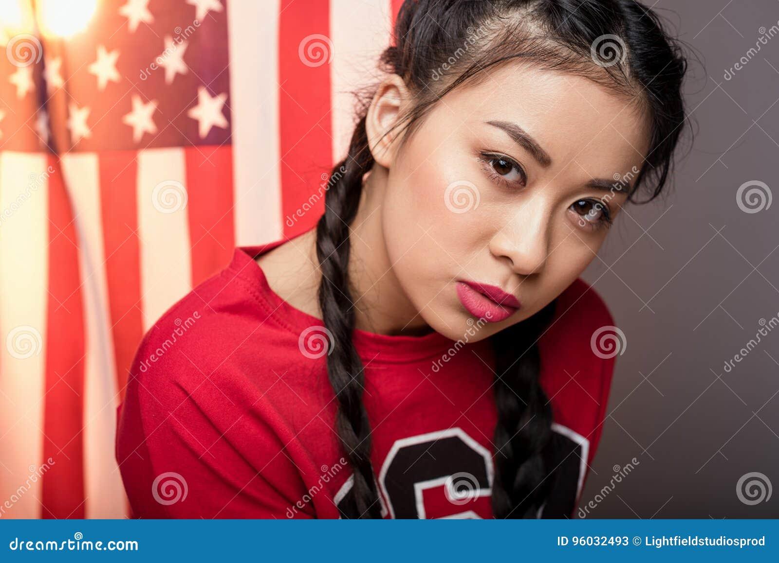 Het jonge Aziatische vrouw stellen voor de vlag van de V.S., Onafhankelijkheidsdag van Amerika