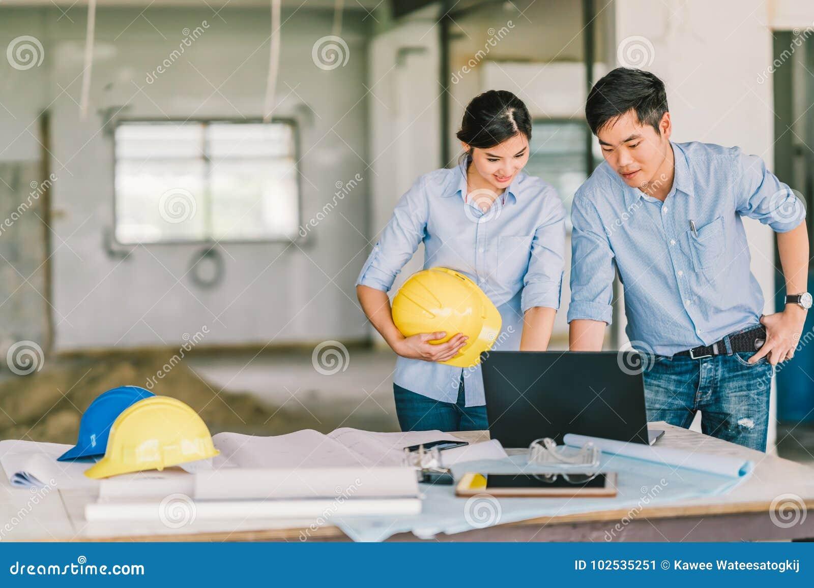 Het jonge Aziatische werk die van het ingenieurspaar samen notitieboekjecomputer met behulp van bij bouwconstructieplaats Het con