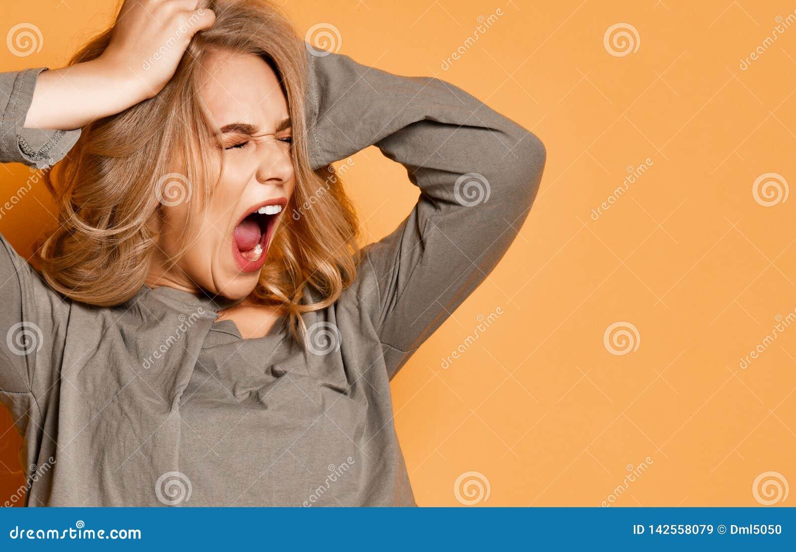 Het jonge blondemeisje in korte blouse heeft in een vreselijke situatie Zij scheurt uit haar haar en schreeuwt luid
