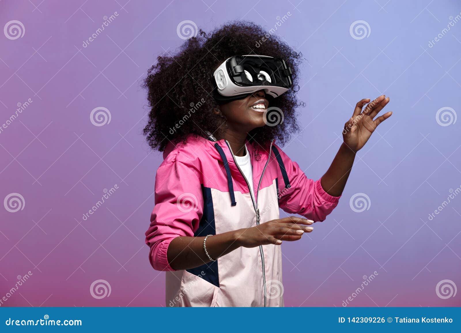 Het jonge bruin-haired krullende meisje van mod. gekleed in de roze blazer gebruikt de virtuele werkelijkheidsglazen in de studio