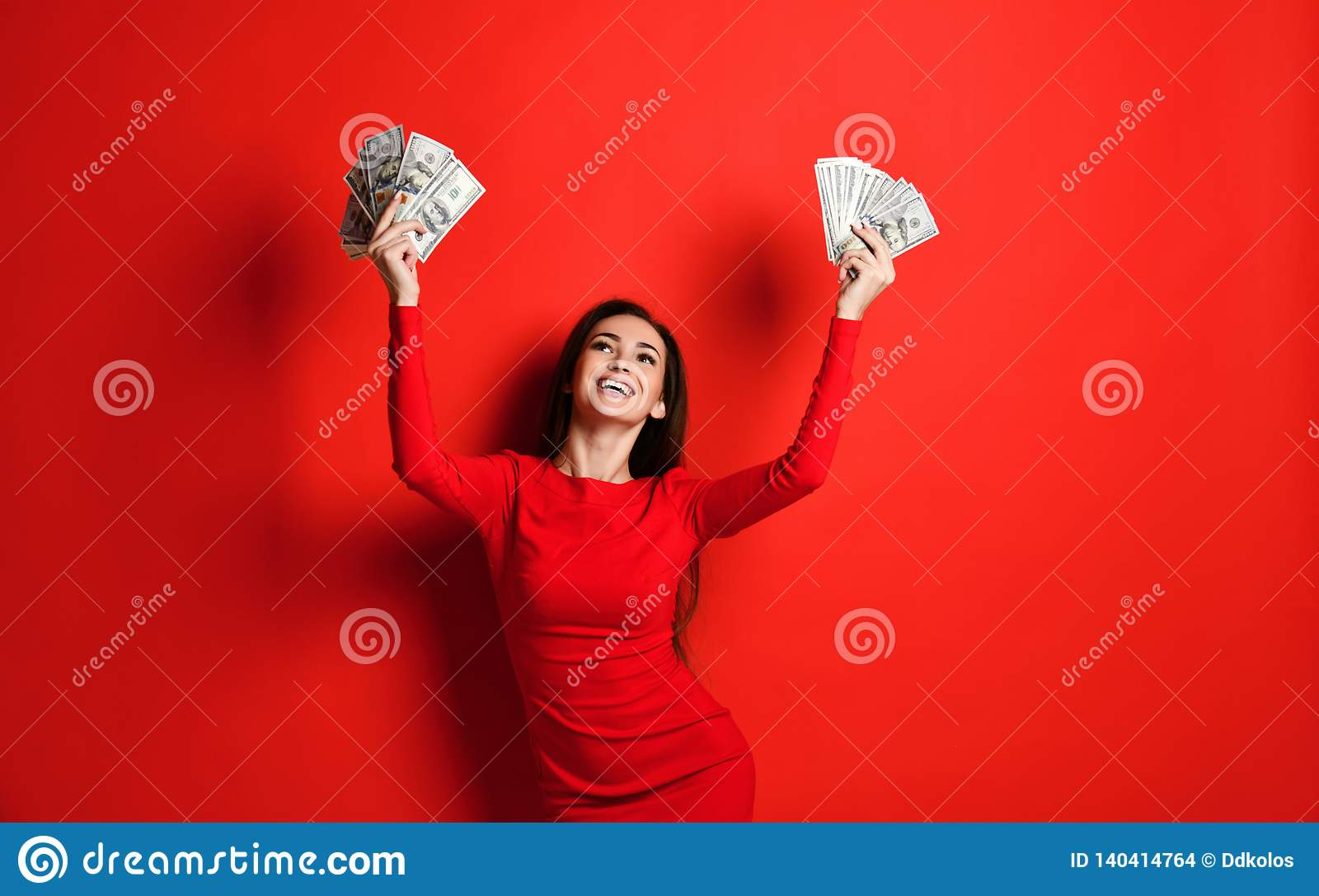 Het jonge brutale brunette in een rode kleding verheugt zich in een hoop van geld in haar handen die zij heeft gewonnen