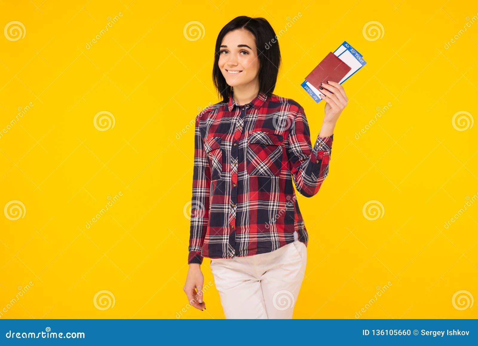Het jonge die glimlachen wekte het kaartje van de het paspoort instapkaart van de studenteholding op gele achtergrond wordt geïso